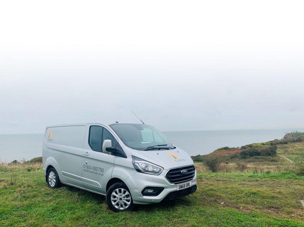 Hcomm van on a cliff overlooking the sea