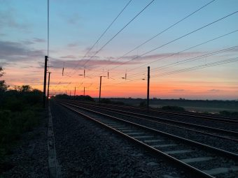 Railway tracks with the sky red and the Sun set